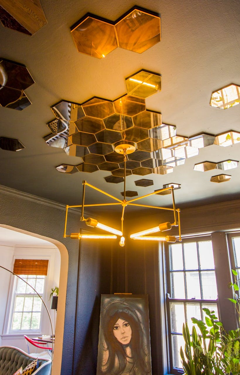 Paint The Wall Color On The Ceiling And Add A Beehive Style Mirror Collage.  We Love How It Enhances The Sparkle Of The Modern Chandelier.